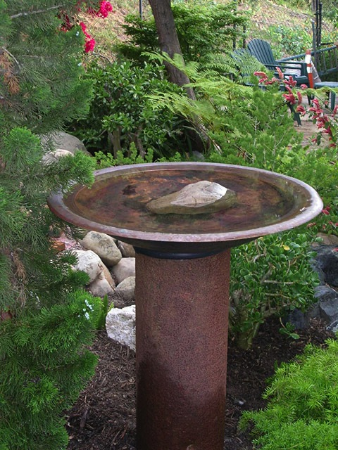 Bird bath made from steel pipe and copper fire pit.