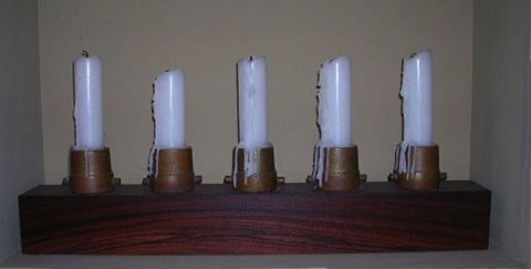 Candle holder made from wood and vintage brass fire nozzles created by artist Tal Avitzur.